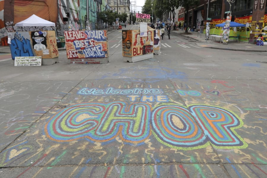 A sign on the street welcomes visitors, Wednesday, June 24, 2020, inside the CHOP (Capitol Hill Occupied Protest) zone in Seattle. The area has been occupied since a police station was largely abandoned after clashes with protesters, but Seattle Mayor Jenny Durkan said Monday that the city would move to wind down the protest zone following several nearby shootings and other incidents that have distracted from changes sought by peaceful protesters opposing racial inequity and police brutality. (AP Photo/Ted S.