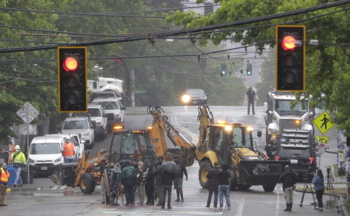 Seattle Department of Transportation workers remove barricades at the intersection of 10th Ave. and Pine St., Tuesday, June 30, 2020 at the CHOP (Capitol Hill Occupied Protest) zone in Seattle. Protesters quickly moved couches, trash cans and other materials in to replace the cleared barricades. The area has been occupied by protesters since Seattle Police pulled back from their East Precinct building following violent clashes with demonstrators earlier in the month. (AP Photo/Ted S.