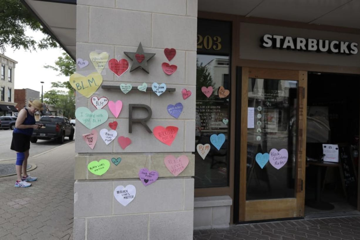 "FILE - In this Thursday, June 4, 2020 file photo, a woman looks at the plywood covering the windows of a Starbucks store in downtown Naperville, Ill., as Naperville residents used hearts to post messages in support of the Black Lives Matter movement. Starbucks is the latest company to say it will pause social-media ads after a campaign led by civil-rights organizations called for an ad boycott of Facebook, saying it doesn't do enough to stop racist and violent content.  Starbucks said Sunday, June 28 that its actions were not part of the ""#StopHateforProfit"" campaign, but that it is pausing its social ads while talking with civil rights organizations and its media partners about how to stop hate speech online.  (AP Photo/Nam Y."