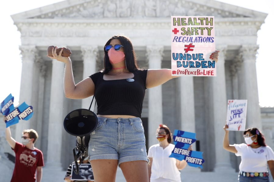 Terrisa Bukovinac, founder of Pro-Life San Francisco, holds a model of a fetus as she and other anti-abortion protesters wait outside the Supreme Court for a decision, Monday, June 29, 2020. The Supreme Court has struck down a Louisiana law regulating abortion clinics, reasserting a commitment to abortion rights over fierce opposition from dissenting conservative justices in the first big abortion case of the Trump era.