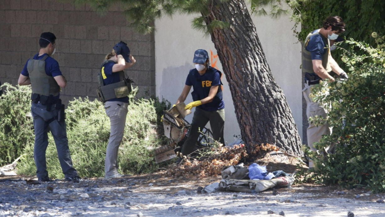 FBI agents examine an area in Paso Robles, Calif., Thursday, June 11, 202, as the investigation into the shooting of a sheriff's deputy early Wednesday continues in the Central Coast city. A man was found fatally shot near where the deputy was wounded, and authorities believe the events are connected. Deputy Nicholas Dreyfus was shot in the face. Authorities say he underwent successful surgery and his prognosis Thursday is good. Authorities have identified the suspect as 26-year-old Mason James Lira and they say he's a transient from the Monterey, Calif., area.