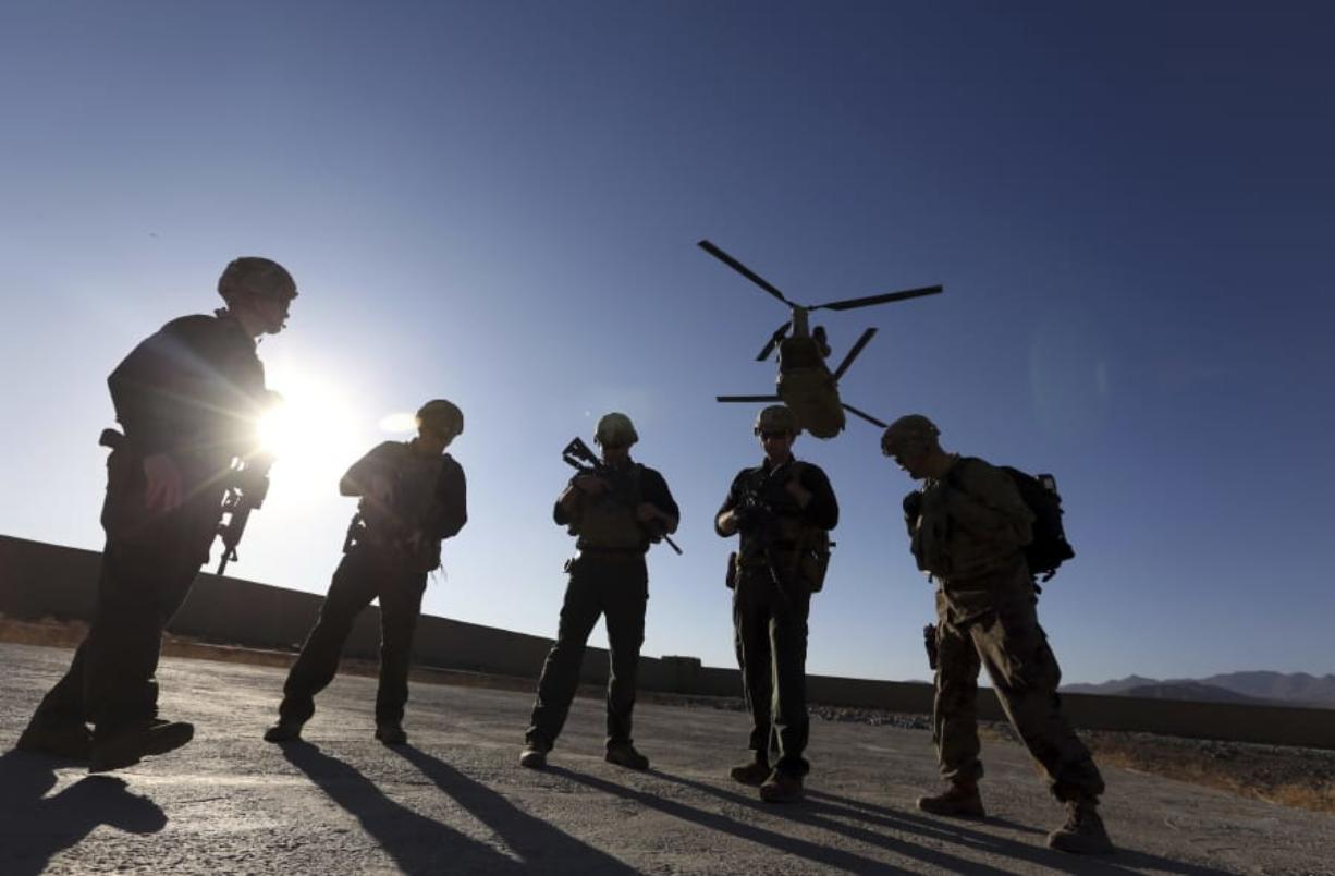 FILE - In this Nov. 30, 2017 file photo, American soldiers wait on the tarmac in Logar province, Afghanistan. Top officials in the White House were aware in early 2019 of classified intelligence indicating Russia was secretly offering bounties to the Taliban for the deaths of Americans, a full year earlier than has been previously reported.