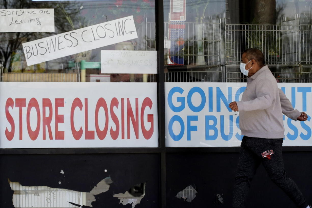 FILE - In this May 21, 2020 file photo, a man looks at signs of a closed store due to COVID-19 in Niles, Ill.   U.S. businesses shed 2.76 million jobs in May, as the economic damage from the historically unrivaled coronavirus outbreak stretched into a third month. The payroll company ADP reported Wednesday that businesses have let go of a combined 22.6 million jobs since March.AP Photo/Nam Y.