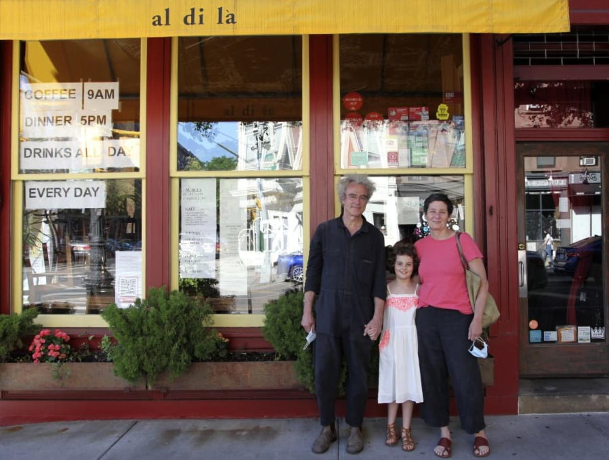 In this June 14, 2020 photo, Emiliano Coppa, left, and chef Anna Klinger pose with their daughter outside their trattoria, Al di La, in the Park Slope neighborhood in the Brooklyn borough of New York. The coronavirus has decimated the restaurant industry, leaving millions unemployed and shuttering spots for good. Many dine-in restaurants have turned to delivery or takeout, like Al di La.