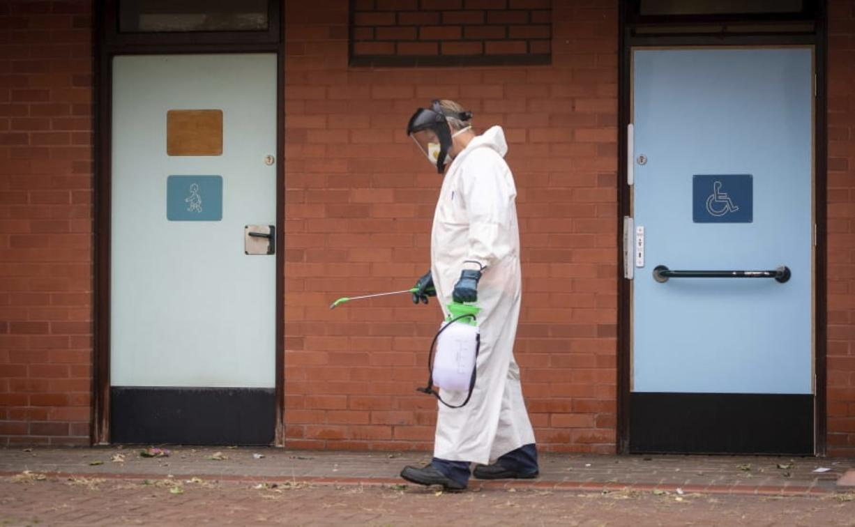 A worker for Leicester City Council disinfects public toilets in Leicester, England, Monday June 29, 2020. The central England city of Leicester is waiting to find out if lockdown restrictions will be extended as a result of a spike in coronavirus infections.
