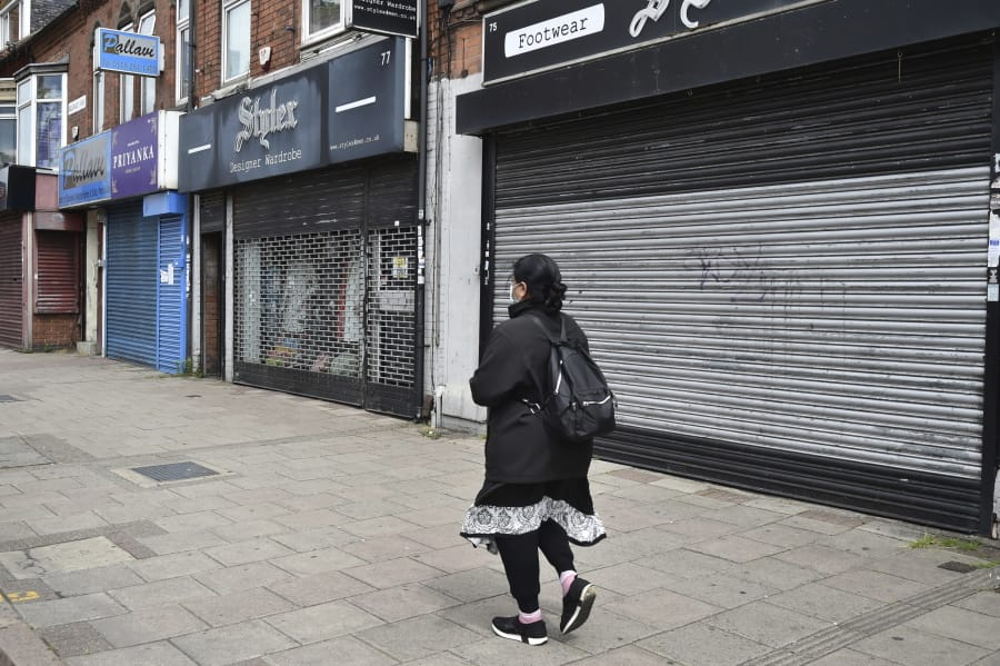 A woman walks past closes shops in Melton Road also known as the Golden Mile in Leicester, England, Tuesday June 30, 2020. The British government has reimposed lockdown restrictions in the English city of Leicester after a spike in coronavirus infections, including the closure of shops that don't sell essential goods and schools.