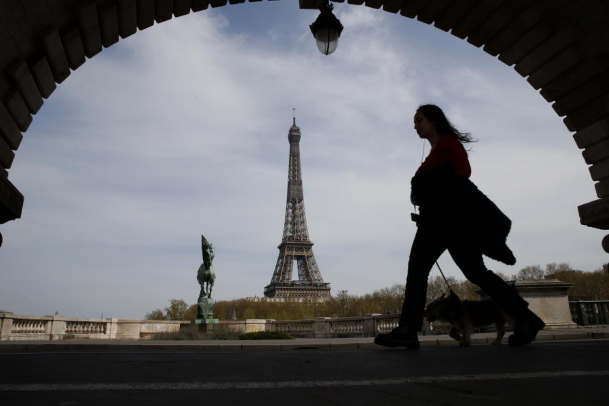 A woman walks her dog on a Paris bridge April 7, with the Eiffel Tower in background, during a nationwide confinement to counter the COVID-19.