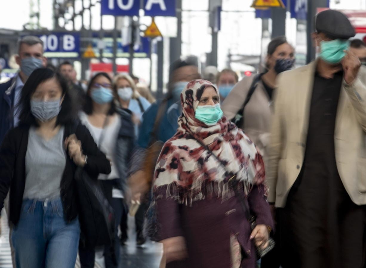 People wear face masks as they leave a train at the central train station in Frankfurt, Germany, Thursday, June 18, 2020.