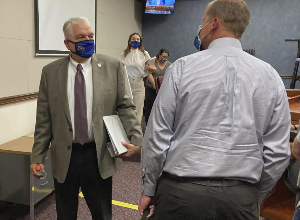 FILE - In this Wednesday, June 24, 2020, file photo, Nevada Gov. Steve Sisolak exits a news conference at the Nevada State Legislature in Carson City, Nev. Sisolak announced Nevada would join California, Washington and North Carolina in requiring individuals wear masks in public places to contain the spread of the coronavirus.