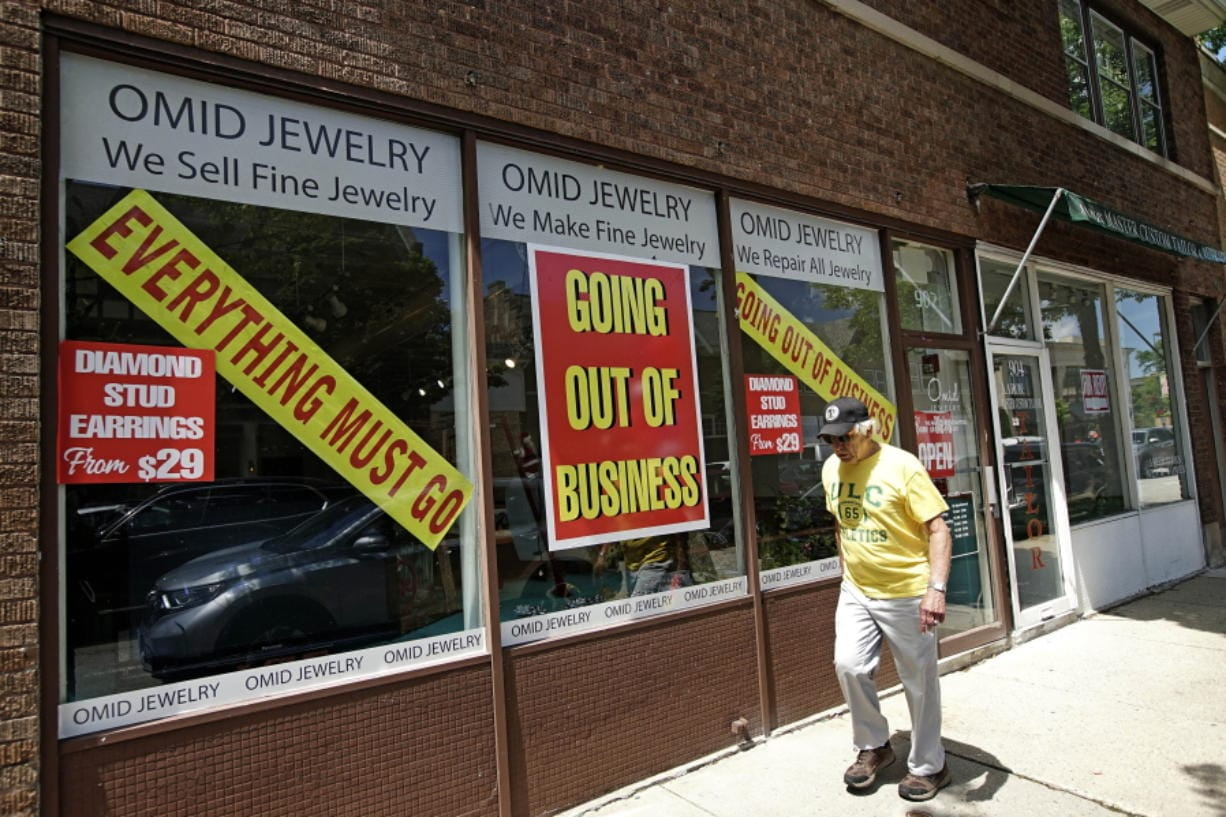 A man walks past a retail store that is going out of business due to the coronavirus pandemic in Winnetka, Ill., Tuesday, June 23, 2020. Illinois Gov. J.B Pritzker announced a package of state grant programs that will help support communities and businesses impacted by the COVID-19 pandemic and unrest in the area. (AP Photo/Nam Y.