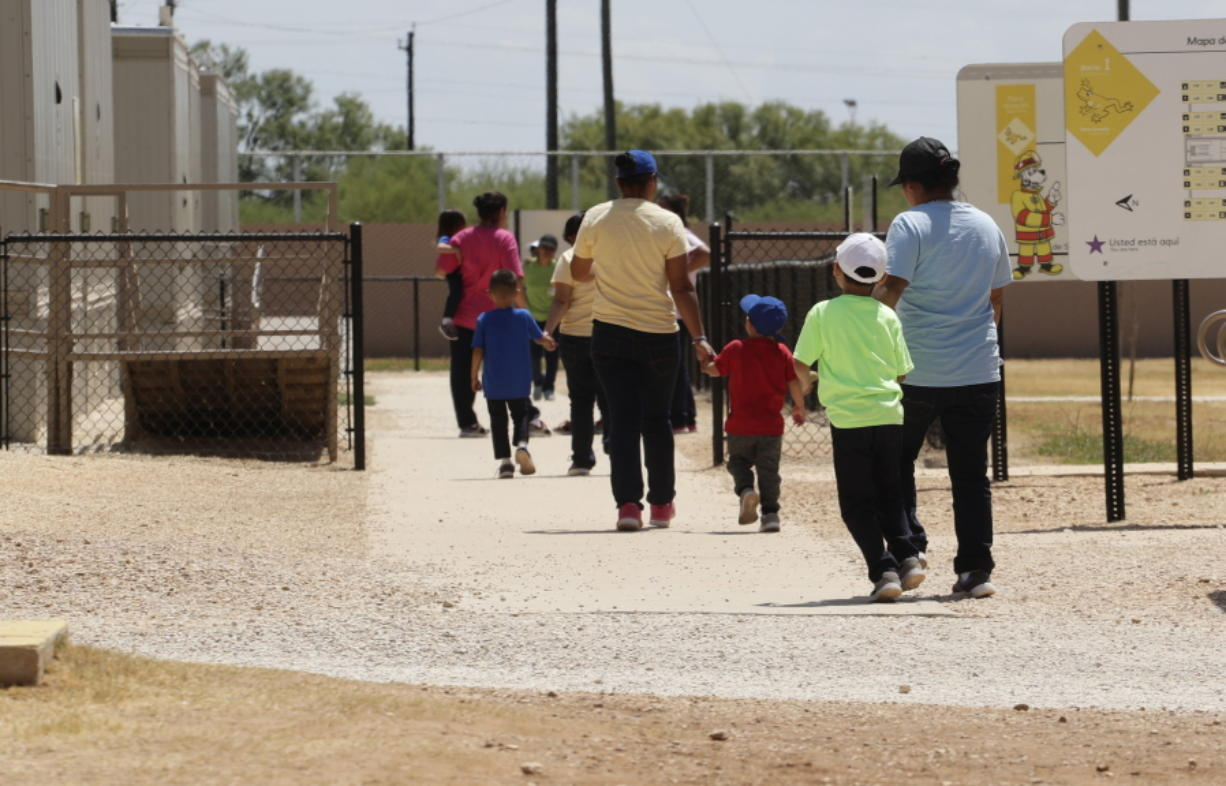 FILE - In this Aug. 23, 2019 file photo, immigrants seeking asylum hold hands as they leave a cafeteria at the ICE South Texas Family Residential Center in Dilley, Texas. The isolation of at least three families at the U.S. Immigration and Customs Enforcement's detention center in Dilley, has raised new fears of the coronavirus spreading through a facility that has long been accused of providing substandard medical care.