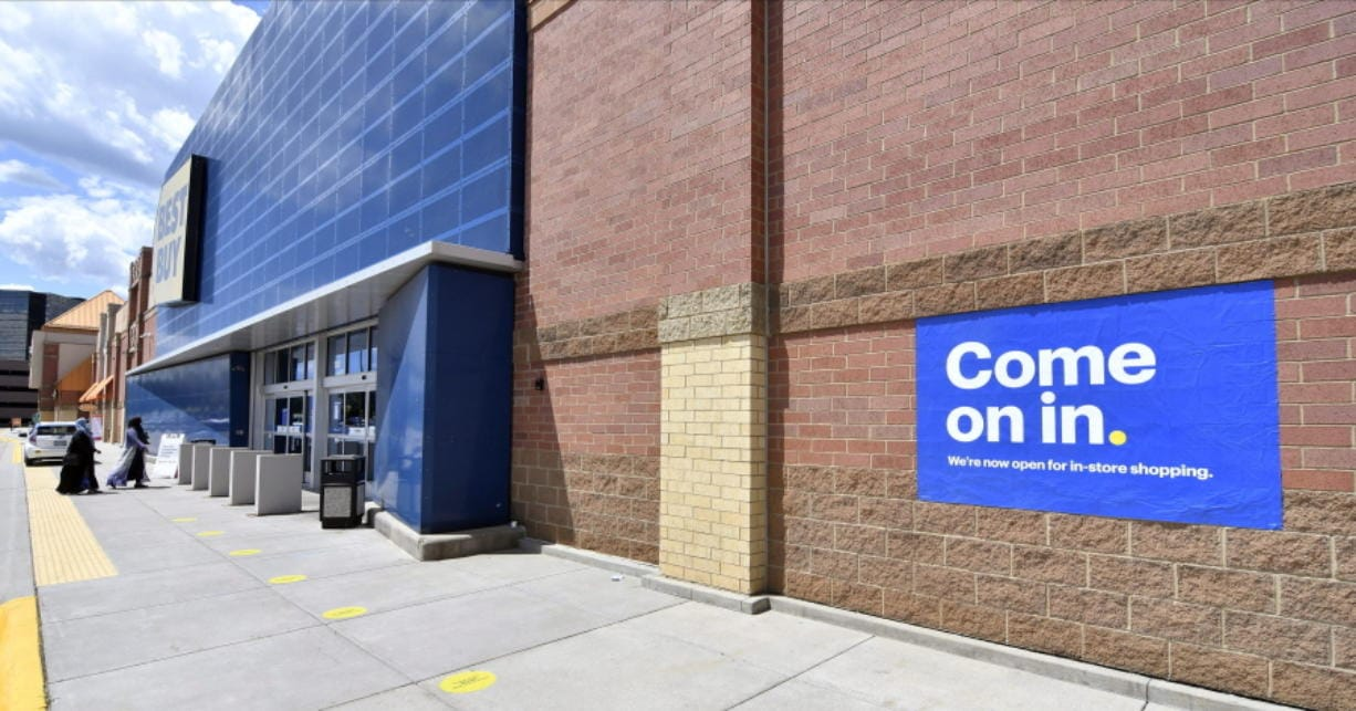 Shoppers, left, head to the entrance as a sign on the outside wall invites customers to shop inside a Best Buy store Wednesday, June 24, 2020 in Richfield, Minn. as restrictions due to the coronavirus have eased in Minnesota.