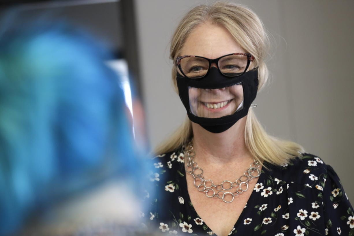 In this June 3, 2020, photo, Chris LaZich, of Fleet Science Center, wears a mask with a window as she talks with Delpha Hanson in San Diego.