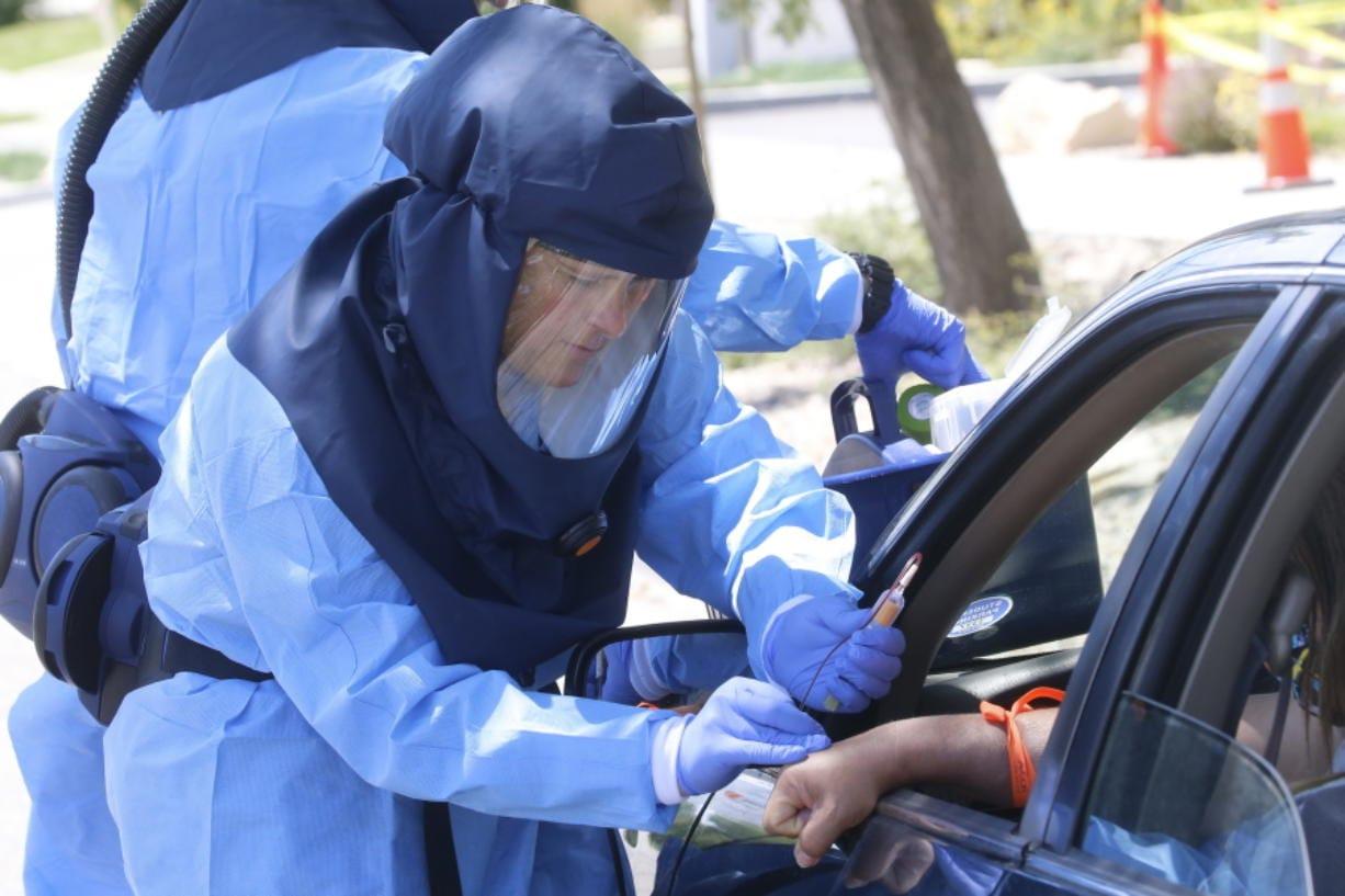 Salt Lake County Health Department's public health nurse Lee Cherie Booth performs a coronavirus anti-body test outside the Salt Lake County Health Department Thursday, June 25, 2020, in Salt Lake City.