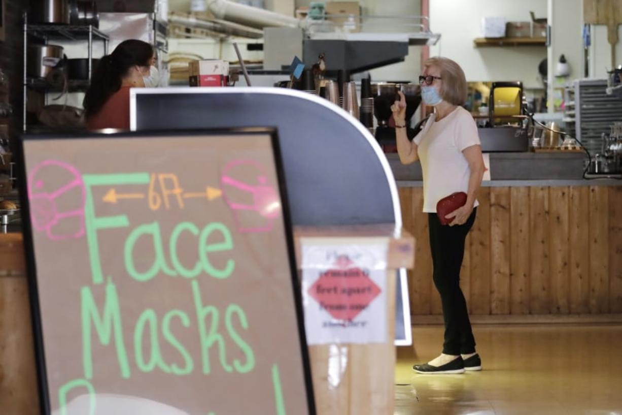 A customer, wearing a mask because of the coronavirus outbreak, puts in an order at a bakery Wednesday, June 17, 2020, in Yakima, Wash. Yakima, Benton and Franklin counties remain in Phase 1, meaning only essential businesses are open; restaurant service is limited to takeout and delivery; and limited outdoor recreation.