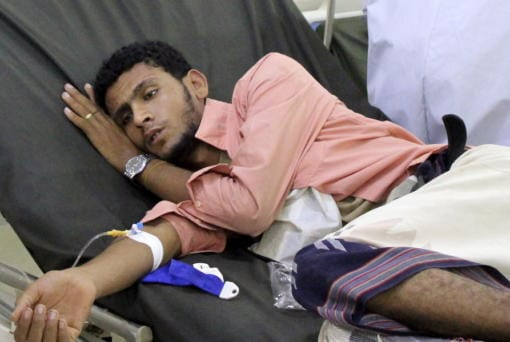 FILE - In this May 12, 2020 file photo, a Yemeni man receives treatment as he lies on a bed at a hospital in Aden, Yemen. Aid organizations are making an urgent plea for donations to shore up their operations in war-torn Yemen, saying they've already been forced to stop some of their work even as the coronavirus rips through the country. The calls for funds come ahead of a UN donor conference, hosted virtually by Saudi Arabia, scheduled to take place Tuesday, June 2, 2020.