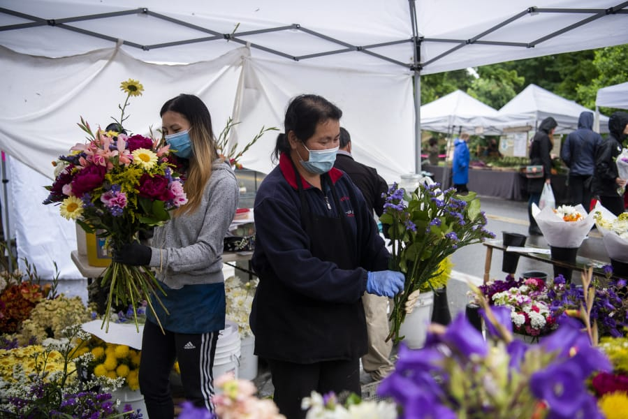 Hlee Huer, left, and Ker Chang with Cheng Blooms make bouquets at the Vancouver Farmer's Market in downtown Vancouver, June 20, 2020. Flower booths were integrated back into the farmers market last week and Chang said she is very happy to be back.