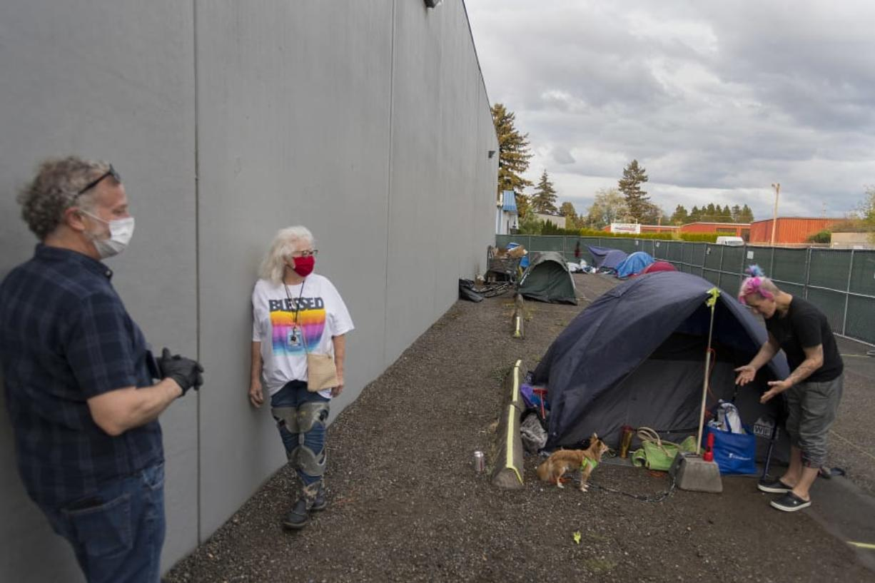 Patrick Quinlan, from left, and Linda Karschney of Living Hope Church chat with Mandi Holper as she settles in for the evening with her dog, Baby, at a temporary homeless encampment outside the church on May 5.