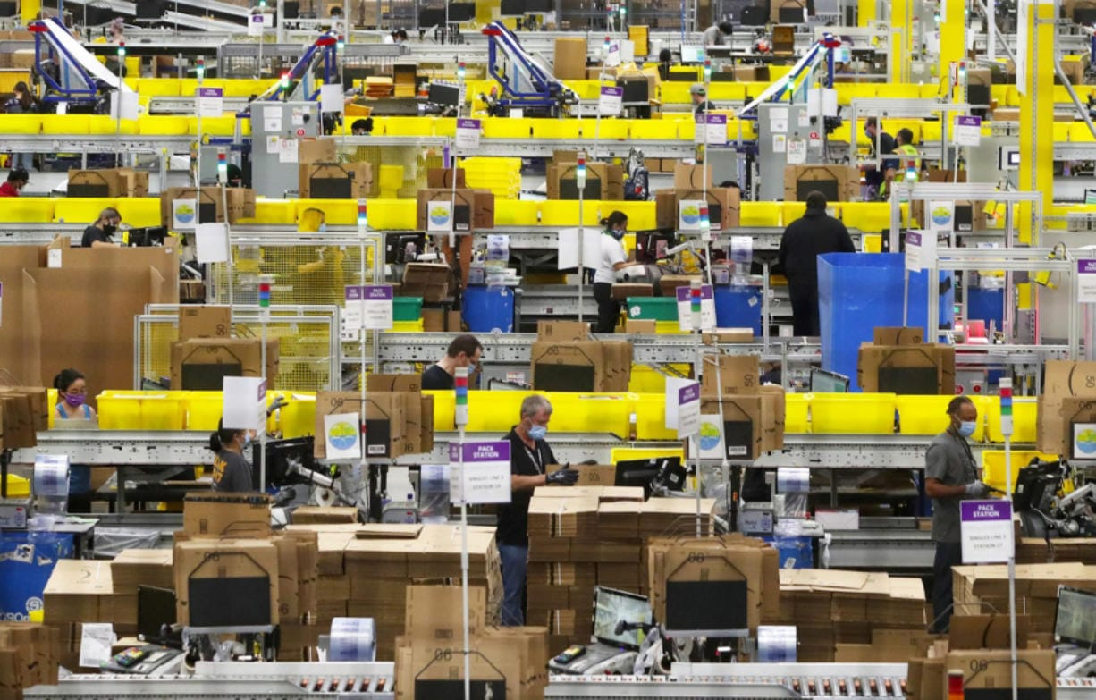 Employees at packing stations are seen at Amazon's Kent fulfillment center, where parts of the company's coronavirus response have been tested, on June 11, 2020.