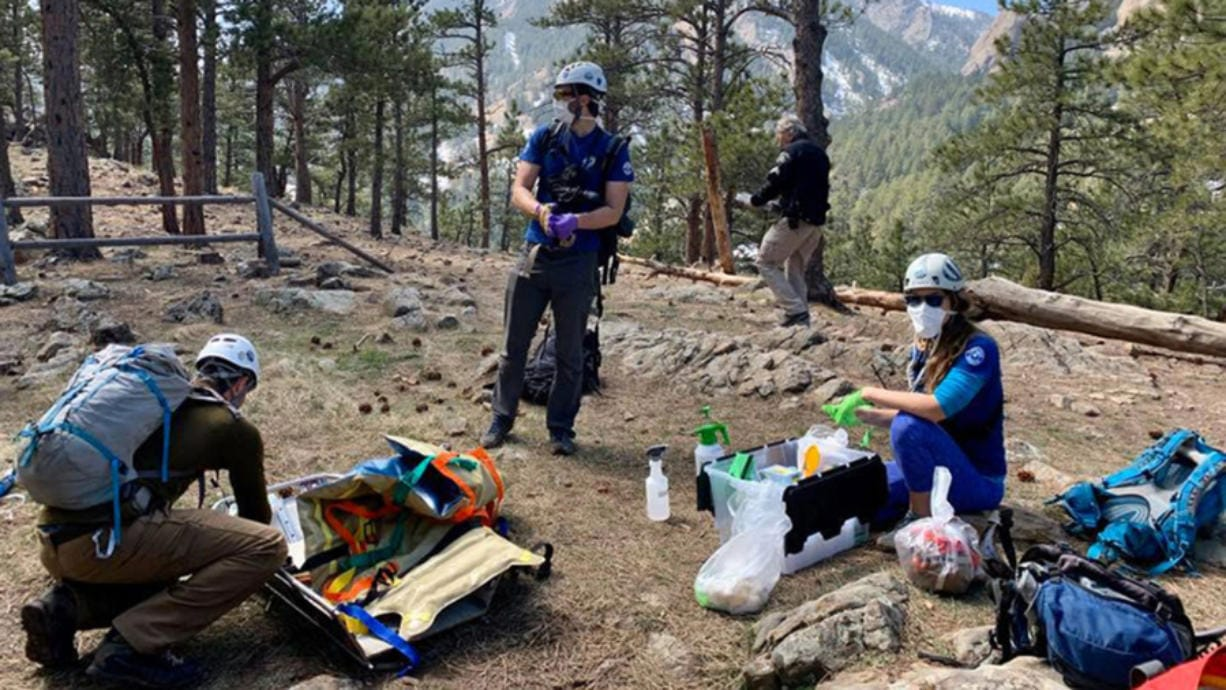 Members of the Rocky Mountain Rescue Group in Colorado wear masks and gloves during a mission earlier this year. The coronavirust pandemic is compounding many of the issues that have challenged search and rescue teams in recent years.
