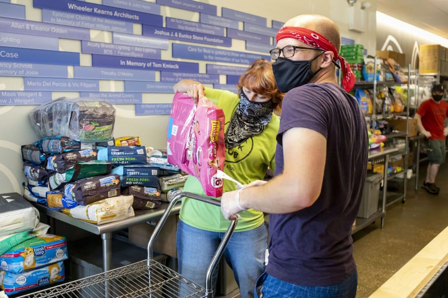 Volunteers Patti Colandrea and Stephen Klozik pack up orders for cats and dogs as the Care for Real pet food pantry reopens on July 2 in Edgewater, Ill.
