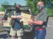 Pete Adams, right, principal officer of Vancouver Firefighters Local 452, receives two boxes of 200 face coverings from Robert Sumrill, first vice commander at Korean War Veterans Association Clark County Chapter 321.