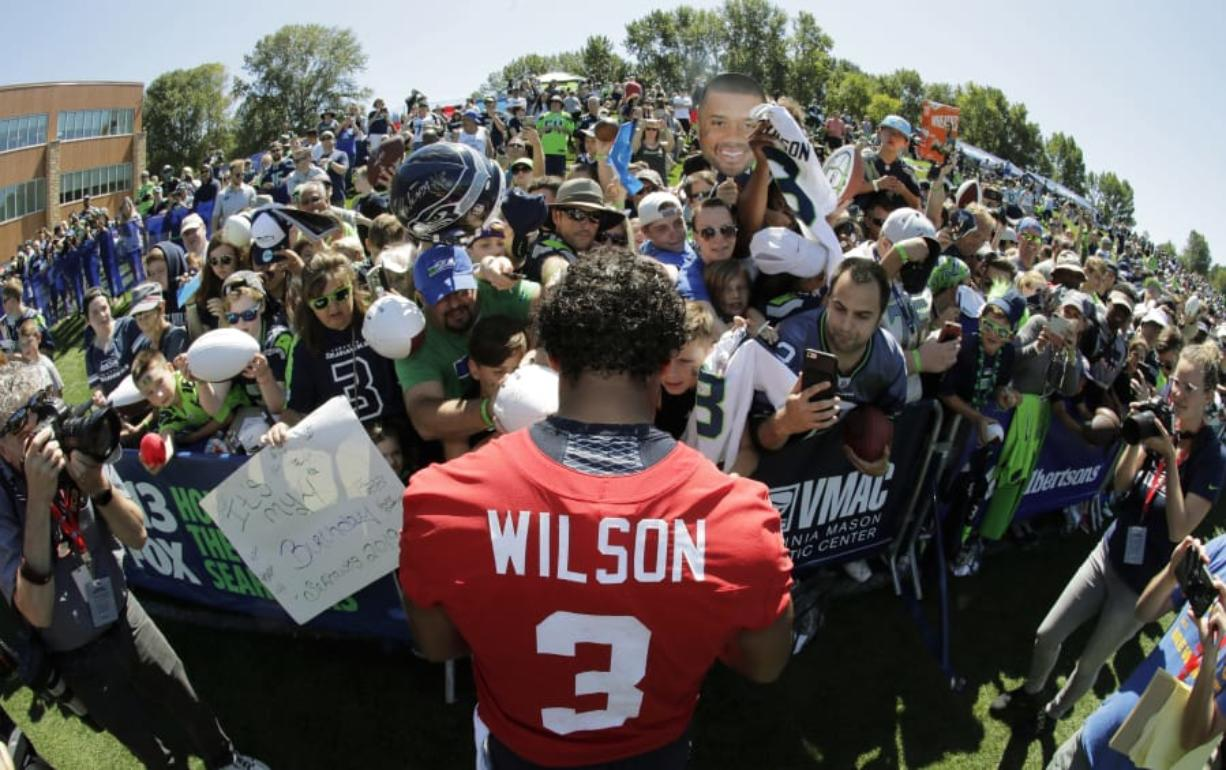 Seattle Seahawks quarterback Russell Wilson (3) signs autographs for fans following a training camp session in 2019 at Renton. The NFL is telling the Seahawks and all other teams training camps for 2020 are on. For Seattle, rookies report on July 21, and all other players on July 28. (AP Photo/Ted S.