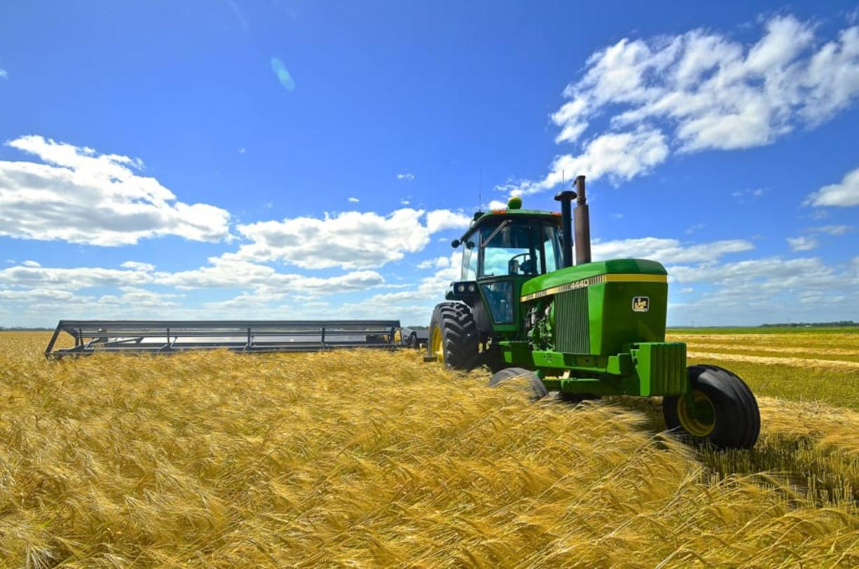 A John Deere 4440 tractor and swather cutting wheat in North Dakota. Worried farmers and business groups are urging the United States and China to fulfill their obligations under the first stage of the trade agreement, even as the coronavirus scrambles its assumptions.