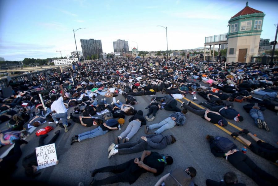 Thousands of marchers lay down on the Burnside Bridge for nine minutes on Tues. evening, symbolizing the amount of time a Minneapolis police officer knelt on George Floyd's neck.  Protests continued for a sixth night in Portland, demonstrating against the death of George Floyd, a black man killed by police in Minneapolis.
