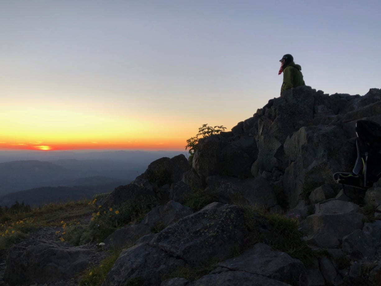 A hiker takes in the sunset atop Silver Star Mountain. At more than 4,300 feet elevation, the view stretches from Mount Rainier to the north to Mount Jefferson to the south.