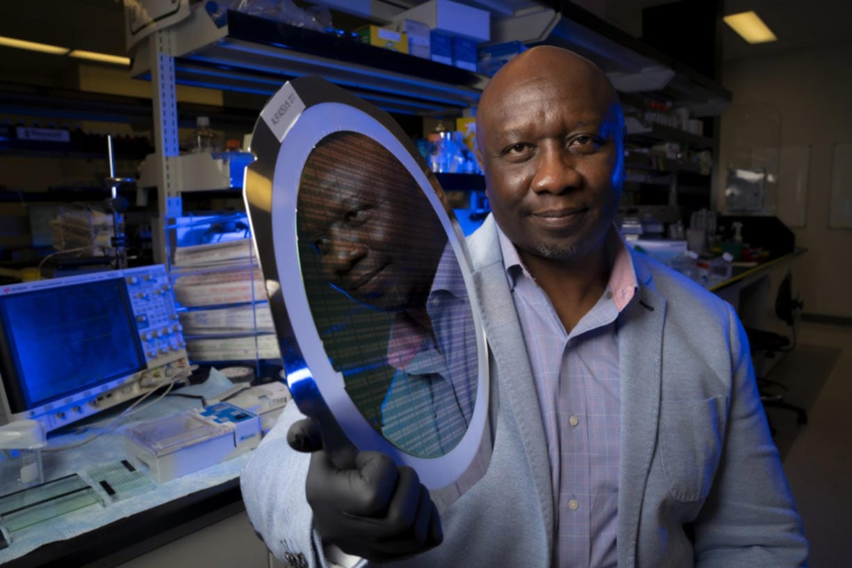 Founder and CEO of Roswell Biotechnologies in Sorrento Valley, Paul Mola holds up a large silicon chip wafer containing hundreds of thousands of sensors.(Nelvin C.