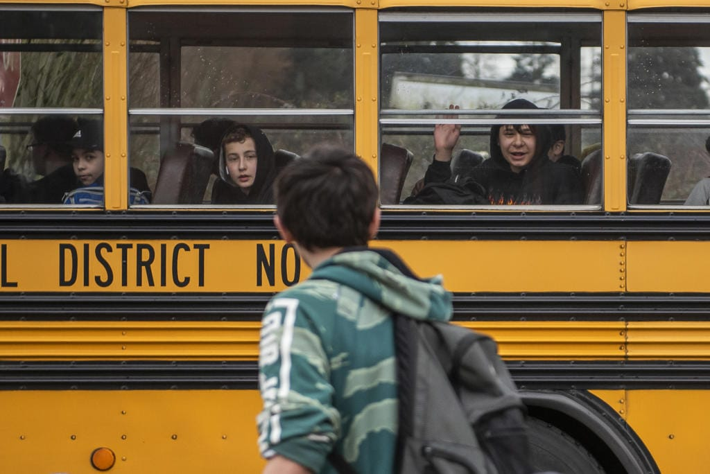 Students wave as their bus pulls away from Covington Middle School on March 13, the final day of in-person school for the 2019-2020 school year. Plans for fall at Clark County school districts are still unsettled.