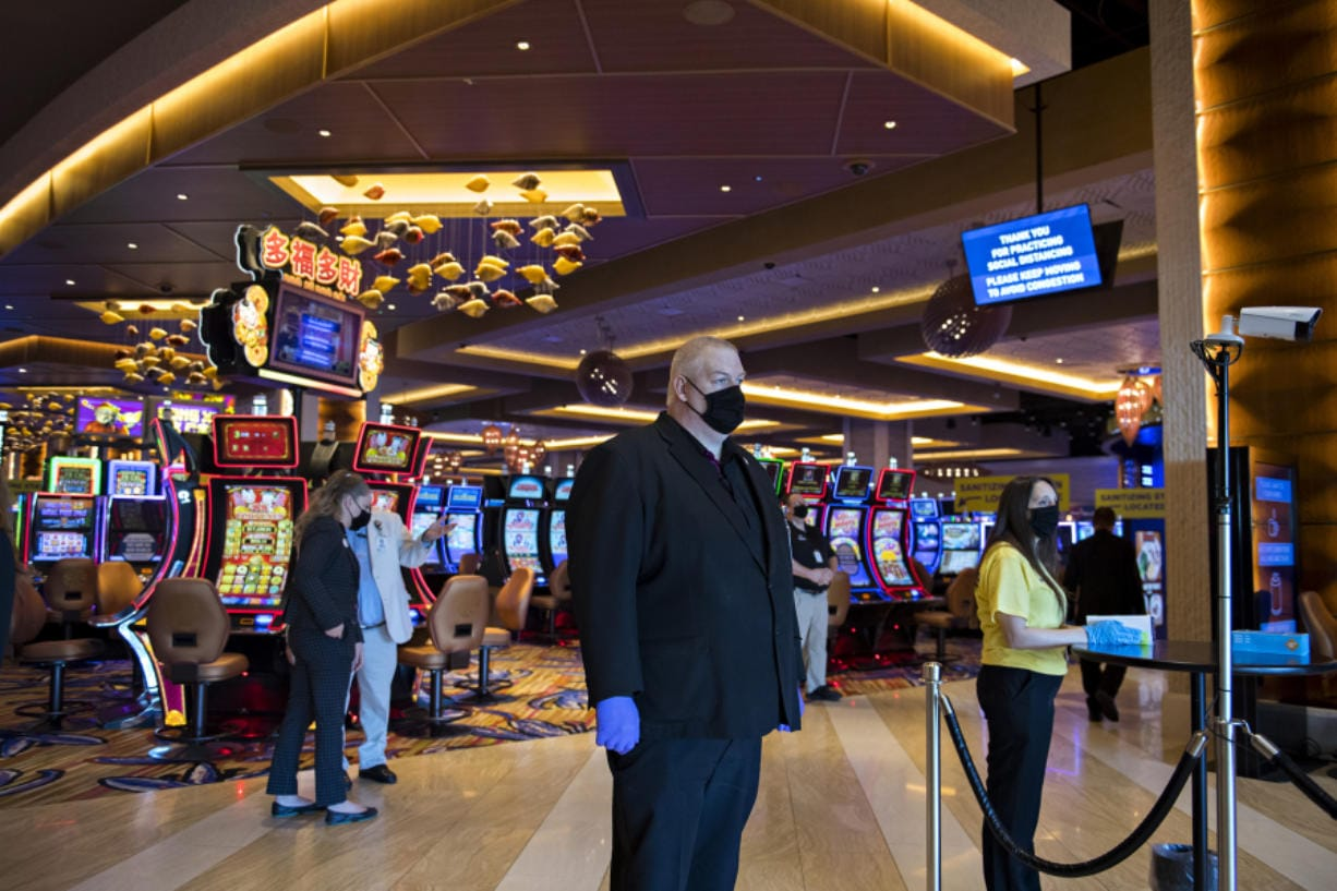Security officer Stephen Henderson, center, wears a mask and gloves as he keeps an eye on the reopening while a thermometer, right, measures the temperature of guests at ilani. The casino says it has invested $1 million in safety measures, but workers have expressed concerns around enforcement.