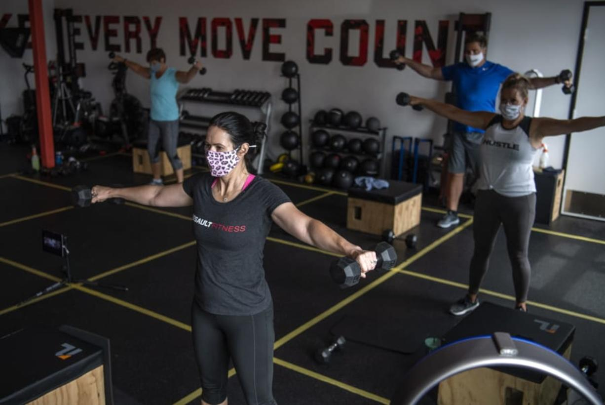 Kedie Sobeck of Los Angeles, Calif., center, works out at Burntown Fitness in east Vancouver. The studio reopened in June after Clark County entered Phase 2. It allow 5 people per class plus the instructor and has taped off sections to allow for social distancing.