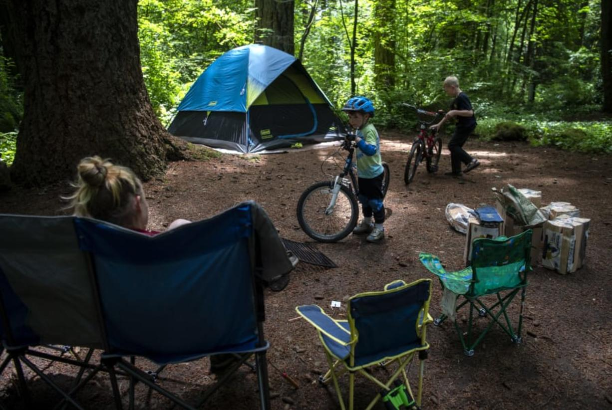 Jack Thompson, 5, of Kingston chats with his mom before taking off on his bike with a new friend from the adjacent campsite at Battle Ground Lake State Park in June. The campground is now open with some distancing restrictions in the group areas. Jack's mom, Leah, said their family had reservations at other campsites but they were canceled due to closures with the pandemic.
