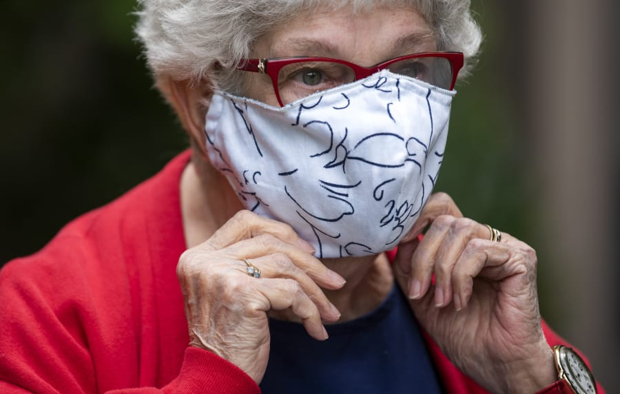 Esther Schrader adjusts her mask as she stands for a photo outside The Quarry in Vancouver.