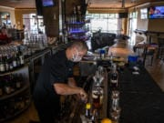 Steve Hilken, restaurant co-owner, makes drinks at Main Event's east location. During Phase 2 of reopening, restaurants must keep a 6-foot distance between tables. Main Event has eliminated bar seating and added one small table next to the bar.