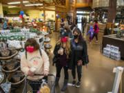 Customers line up Wednesday to check out after shopping at Chuck's Produce in Salmon Creek. Signs are posted at the entrance of the store reminding customers that face coverings are mandatory statewide.