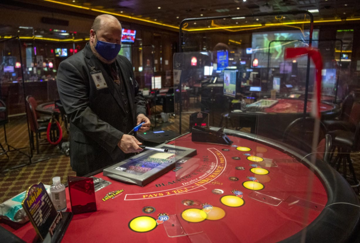 Gary Pfannes, an on-duty manager, demonstrates the use of a germicidal wand to sanitize casino chips in between use Wednesday at The Palace Casino in La Center. The Palace reopened Wednesday.