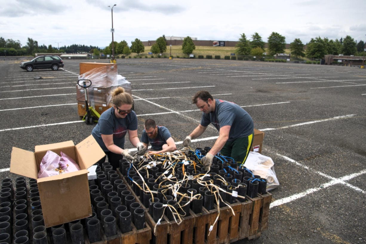 Western Display Fireworks crew member Alisa Williams, from left, pyrotechnician Reggie Edwards and lead pyrotechnician Chad Williams prepare fuses, fireworks and launchers in a parking lot at the Clark County Event Center at the Fairgrounds on Saturday. The no-audience show was to be broadcast live on Fox-12 TV for viewers to enjoy at home. Most Fourth of July fireworks events throughout the region, including the annual show at Fort Vancouver, were canceled this year due to the coronavirus pandemic.
