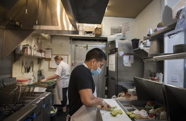 Owner Marian Adams-Manuel, background left, works with chef Vale Martinez in the busy kitchen of Frontier Public House on Tuesday. The Vancouver restaurant received Paycheck Protection Program loans to help bridge the financial gap caused by COVID-19.