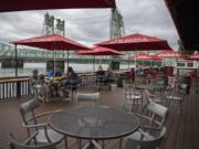 Customers at Who Song & Larry's practice social distancing while enjoying lunch with a Columbia River view on Tuesday. Owners of the restaurant intend to stay in the location until at least 2041.