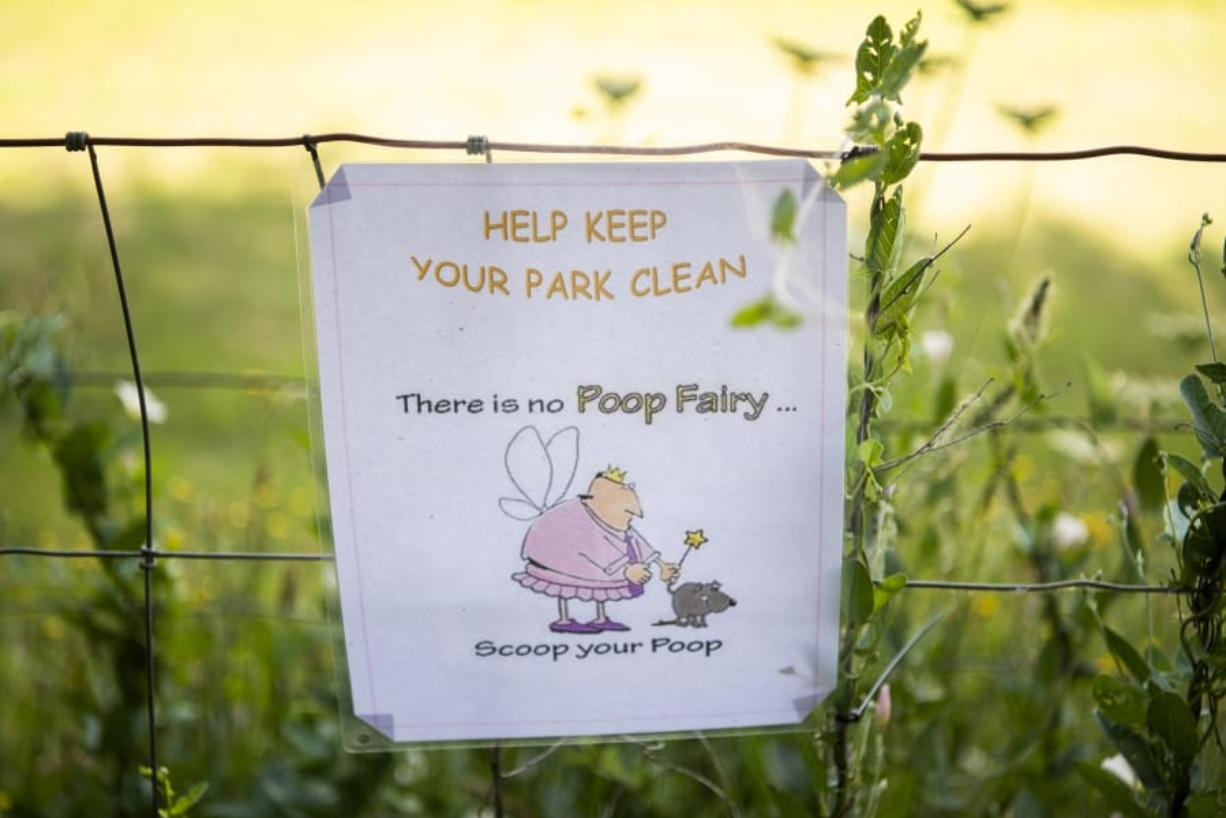 Signs are posted around Ike Dog Park to remind people to pick up after their dogs.