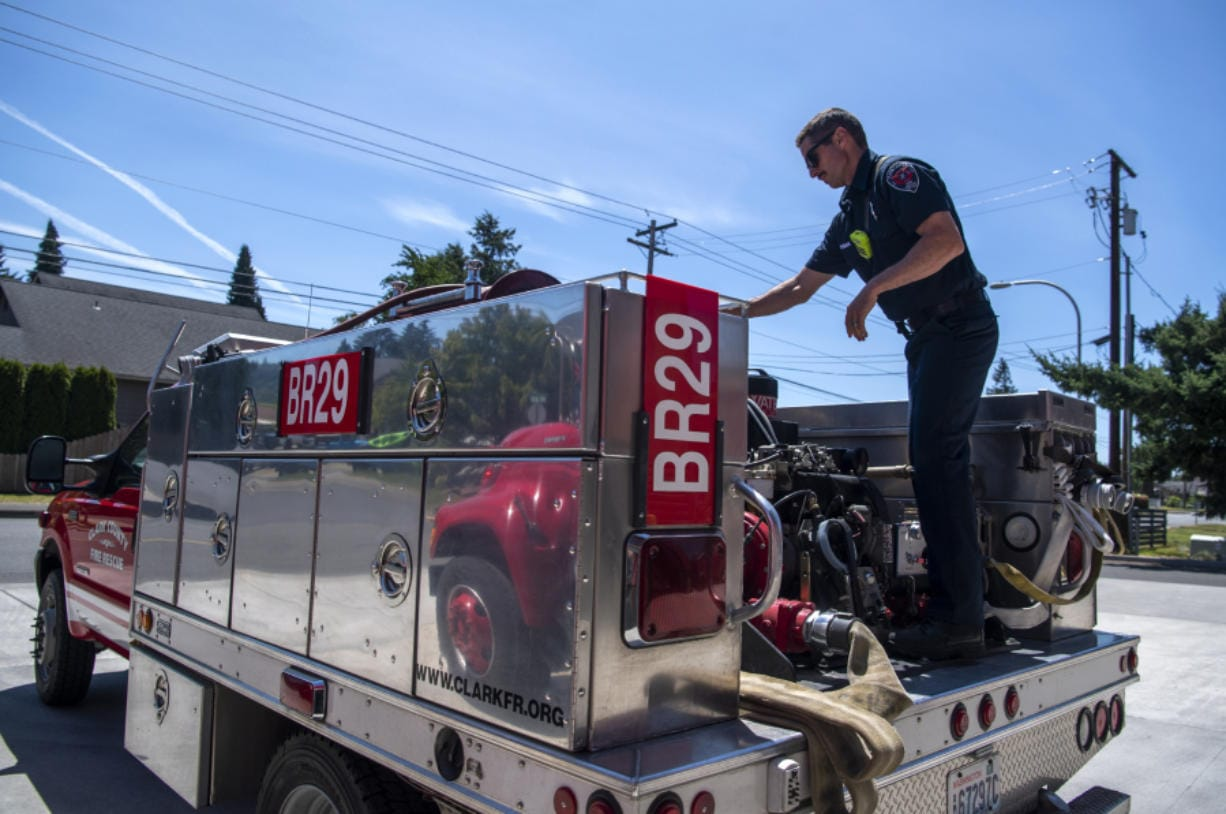 Clark County Fire & Rescue firefighter Ian Fagan performs a routine check on a brush unit water pump Thursday at Station 29 in Woodland.