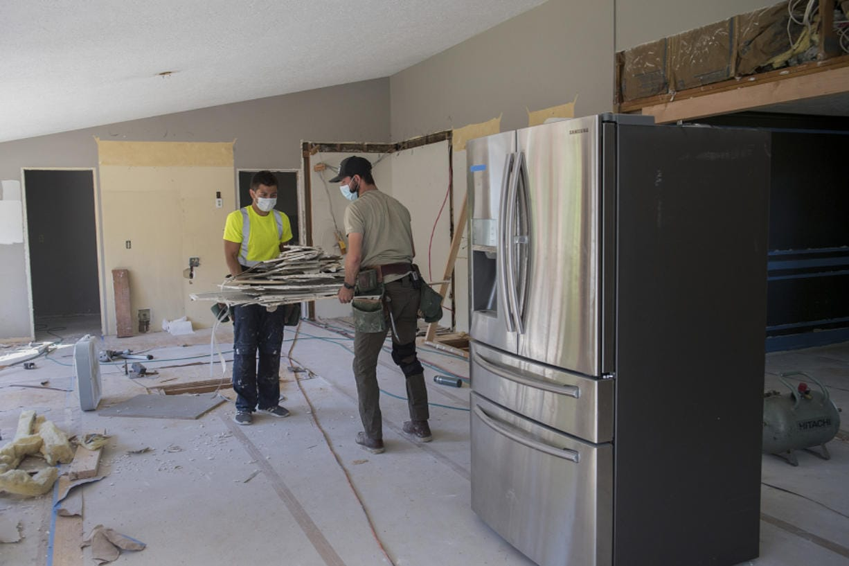 Luke Schlecht, left, and William Jones of Foxbrigade LLC lend a hand to the renovation of a kitchen at a home in Salmon Creek. Local contractors say common home areas like kitchens, family rooms, finished basements and covered patios are all in high demand while families are stuck at home during the COVID-19 pandemic.