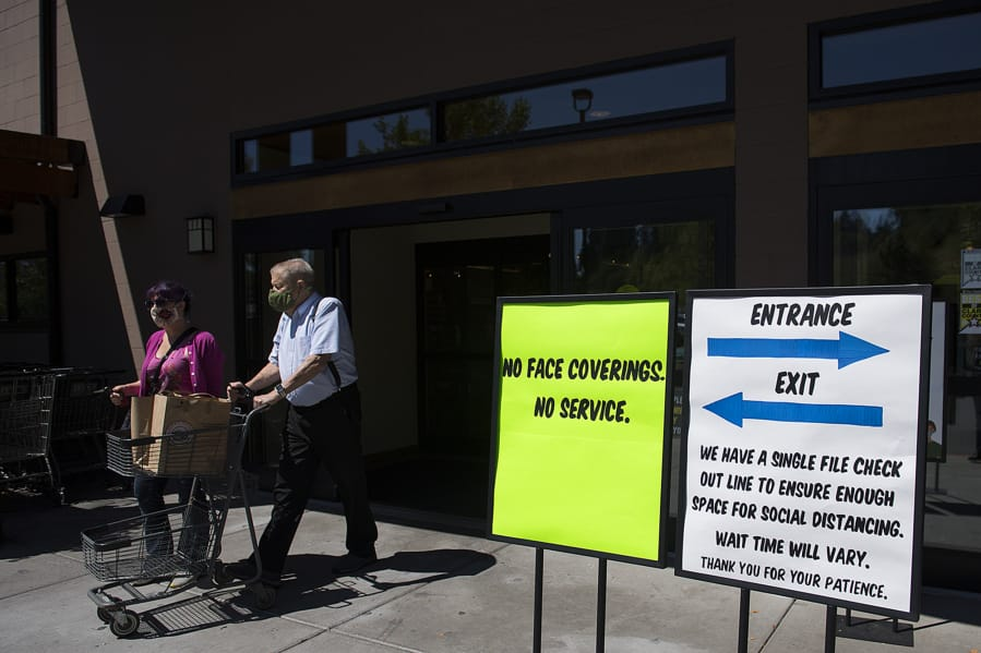 Kirsten Johnson of Vancouver, left, and her father, Ron, are in compliance with store and state policy while wearing protective face masks as they leave Chuck's Produce & Street Market in Salmon Creek with their groceries on Tuesday afternoon.