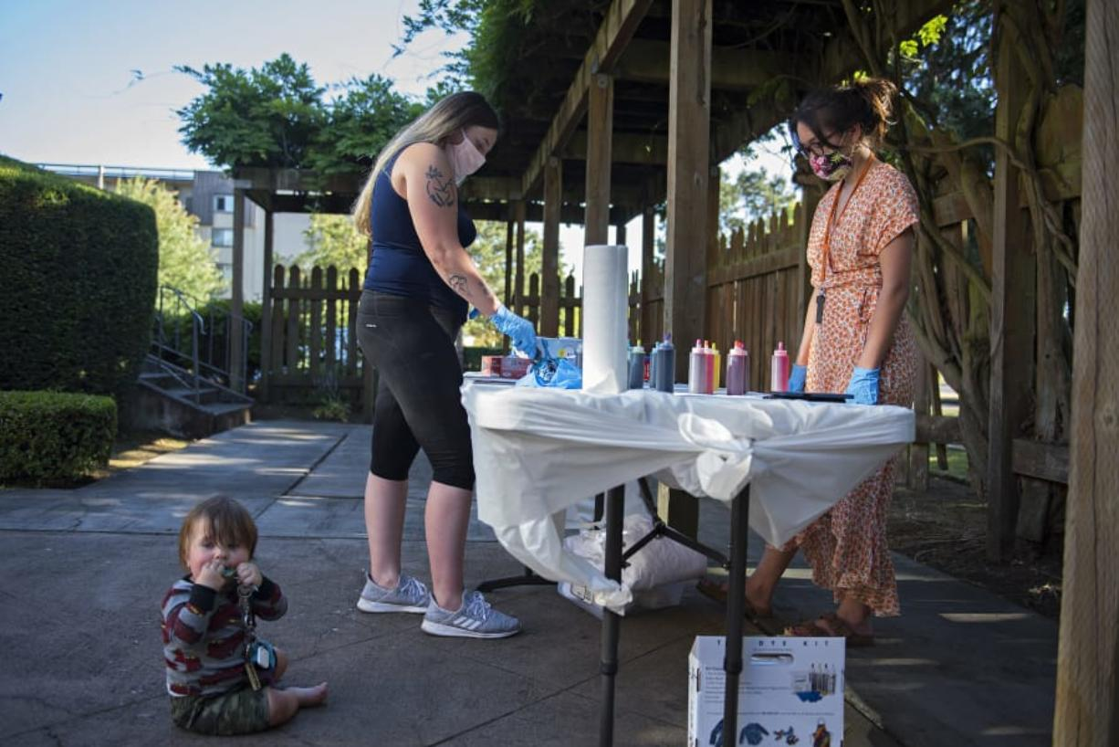 Carter Campbell, 8 months, from left, joins his mom, Breeanna Campbell, as she creates a colorful tie-dye shirt with the help of Julie Tappan, independent living skills resource specialist, at the YWCA on Tuesday evening. The summer celebration was for young people who are participating in YWCA Clark County's Independent Living Skills program. These youth have all aged out of the foster care system and are learning to live on their own.