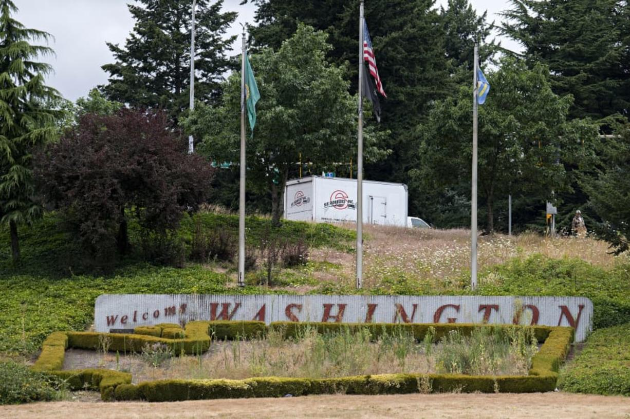 "The ""Welcome to Washington"" sign that greets motorists as they enter Vancouver on Interstate 5, which usually features a colorful floral display, has become overgrown with weeds. The COVID-19 pandemic prevented the normal spring replanting of the sign's flower bed."