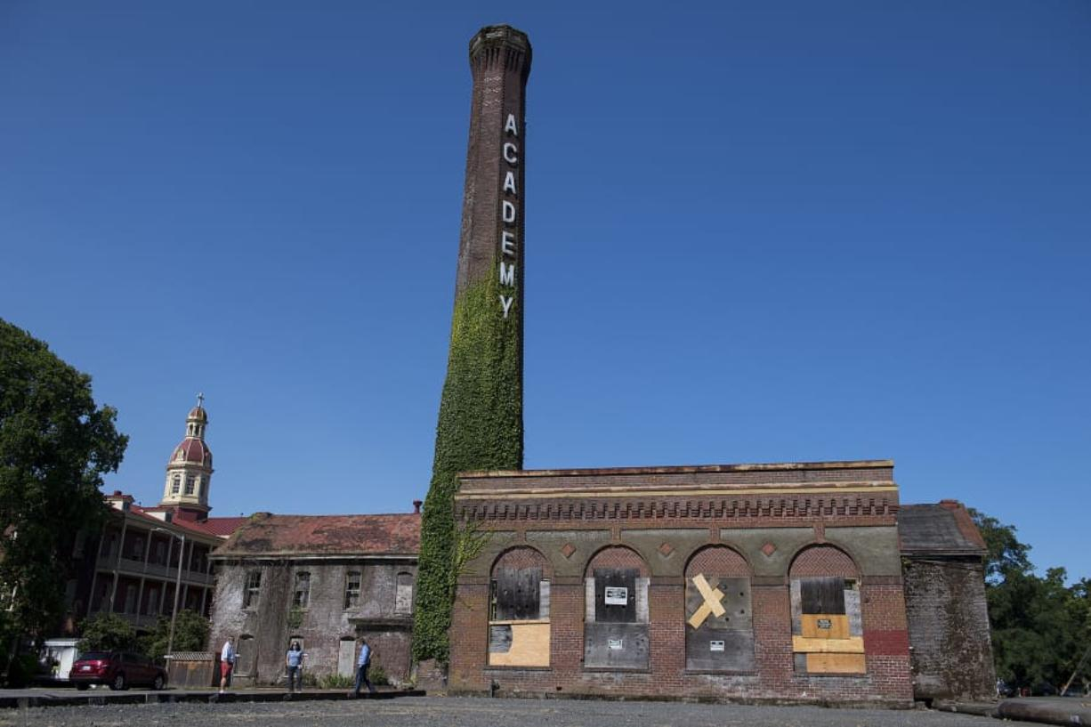 Members of The Historic Trust decided to give up hope of preserving the historic smokestack and boiler building, right, at the Providence Academy, because they couldn't justify the high costs.