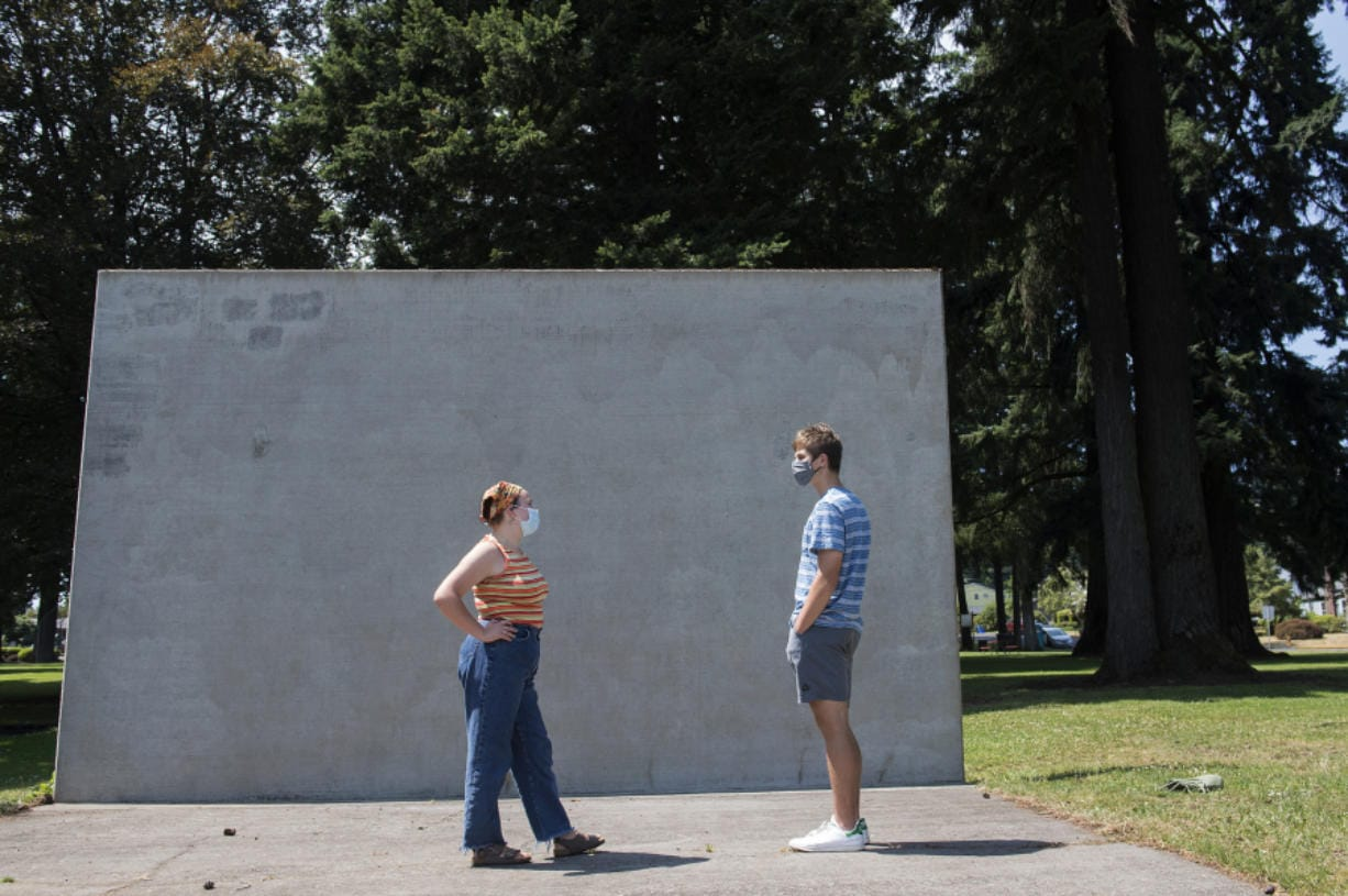 Camas High School rising seniors Kiana Gouveia, left, and Eli McMillan, both 17, pause to chat Tuesday afternoon at Crown Park. The pair had been writing messages on the wall in chalk to support the Black Lives Matter movement, but the murals have repeatedly been removed.